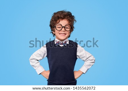 Smart little boy with curly hair wearing nerdy glasses and school uniform smiling for camera while keeping hands on waist against blue background