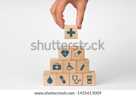 Concept of Insurance for your health, Hand hold wooden block with icon healthcare medical #1435613009