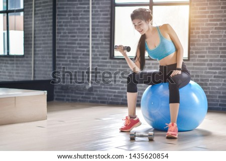 Beautiful fitness woman lifting dumbbell in the morning with ball to ell-developed muscles by strength training in gym #1435620854