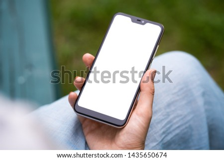 Pretty brunette teenage girl with smartphone outdoors in park. Closeup of female hands and smart phone with isolated white screen. Mock-up concept. #1435650674