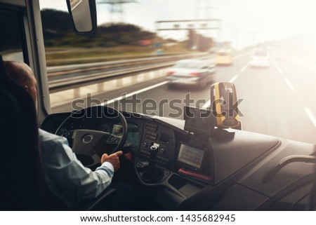 Interior of cab airport transfer bus with driver in motion on fast speed by highway #1435682945