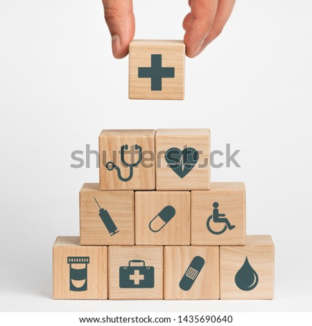 Concept of Insurance for your health, Hand hold wooden block with icon healthcare medical #1435690640