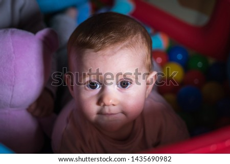 close-up newborn with red hair playing and looking into the room #1435690982