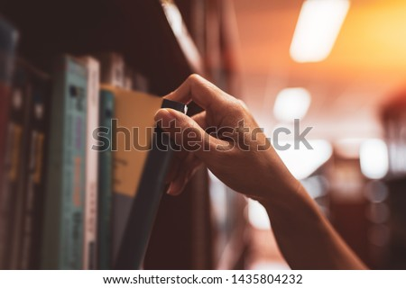 Image of a hand selecting a book from a bookshelf #1435804232