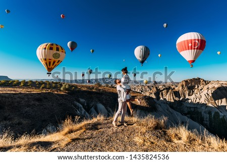 Happy couple in Cappadocia. The man proposed to the girl. Honeymoon in Cappadocia. Couple at the balloon festival. Couple travels the world. The Landscapes Of Cappadocia #1435824536