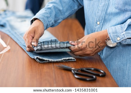 Tailor working with blue denim jeans. Tailor hem the blue jeans. #1435831001
