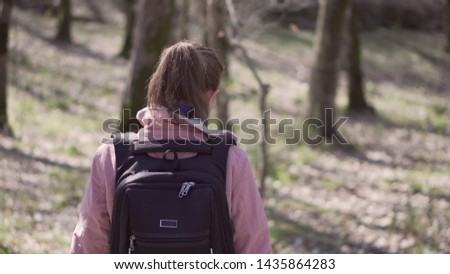 Girl with a dog and a backpack walking in the autumn forest. #1435864283