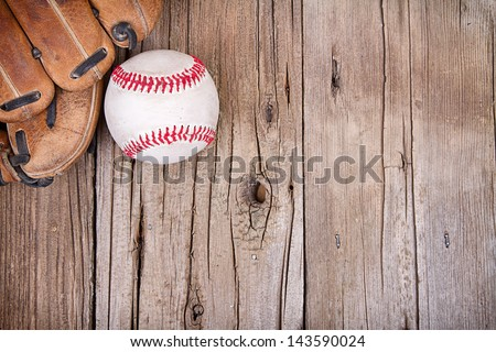 Baseball and mitt on rustic wooden background Royalty-Free Stock Photo #143590024