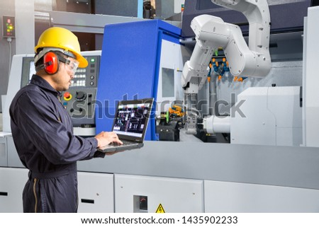 Maintenance engineer using laptop computer control automatic robotic hand with CNC machine in smart factory, Industry 4.0 concept #1435902233