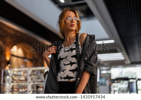 Beautiful urban young hipster woman in trendy glasses in a trendy t-shirt with a pattern in a stylish jacket posing in a shopping center. Red-haired modern girl fashion model indoors. American style. #1435917434