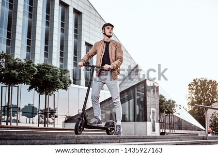 Young attractive student is driving his scooter neat interesting glass building at bright sunny day. #1435927163