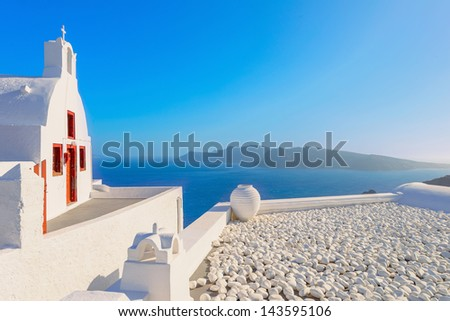 Greece famous Santorini island in Cyclades, panoramic view of traditional whitewashed church with caldera sea and volcano island in background