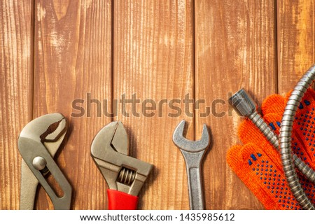 Necessary set of tools for plumbers on a vintage wooden wooden background. Also space for advertising. #1435985612