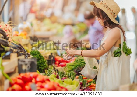 Woman is chooses  fruits and vegetables at food market. Reusable eco bag for shopping. Zero waste concept. #1435991630