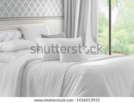 Luxury bedroom that opens with French doors onto a terrace. King bed with white linens and pillows. Interior with garden view window, bed with white bed linen and curtains. #1436053931