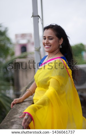 Young and beautiful Indian Bengali brunette woman in Indian traditional dress yellow sari and blue blouse standing on rooftop under blue sky with clouds with her sari blown in air. Indian lifestyle  #1436061737