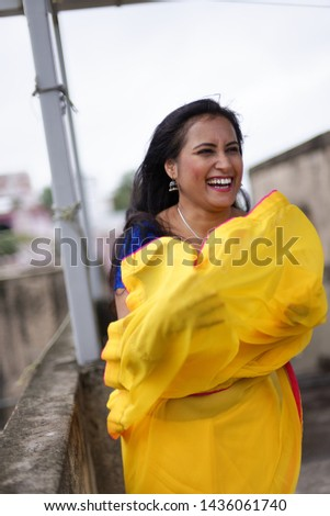 Young and beautiful Indian Bengali brunette woman in Indian traditional dress yellow sari and blue blouse standing on rooftop under blue sky with clouds with her sari blown in air. Indian lifestyle  #1436061740