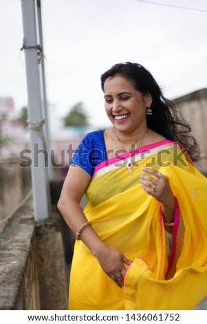 Young and beautiful Indian Bengali brunette woman in Indian traditional dress yellow sari and blue blouse standing on rooftop under blue sky with clouds with her sari blown in air. Indian lifestyle  #1436061752