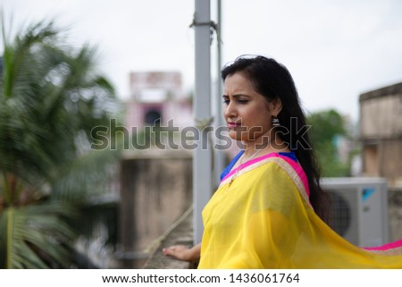Young and beautiful Indian Bengali brunette woman in Indian traditional dress yellow sari and blue blouse standing on rooftop under blue sky with clouds with her sari blown in air. Indian lifestyle  #1436061764