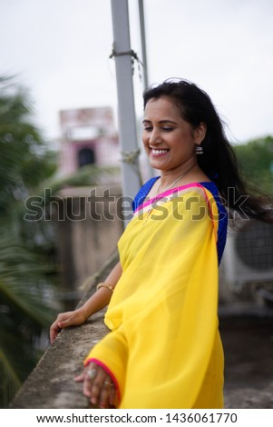 Young and beautiful Indian Bengali brunette woman in Indian traditional dress yellow sari and blue blouse standing on rooftop under blue sky with clouds with her sari blown in air. Indian lifestyle  #1436061770
