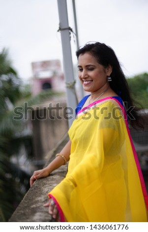 Young and beautiful Indian Bengali brunette woman in Indian traditional dress yellow sari and blue blouse standing on rooftop under blue sky with clouds with her sari blown in air. Indian lifestyle  #1436061776