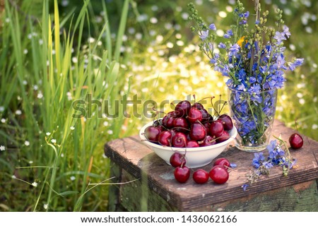 Sweet cherry berries on a white plate on a wooden table with lilac flowers, close up, still life. Top view #1436062166