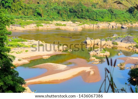 this pic shows Mekong river in Thailand and Laos areas, the  river has many rock islands and forest on riverside  and has fisherman with his boat fishing in the river