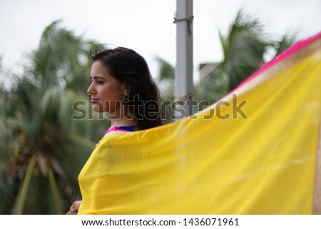 Young and beautiful Indian Bengali brunette woman in Indian traditional dress yellow sari and blue blouse standing on rooftop under blue sky with clouds with her sari blown in air. Indian lifestyle  #1436071961