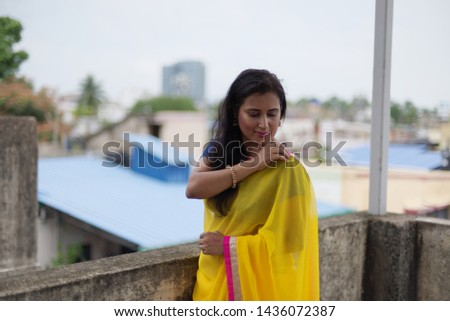 Young and beautiful Indian Bengali brunette woman in Indian traditional dress yellow sari and blue blouse is standing thoughtfully leaning on rooftop wall under blue sky with clouds. Indian lifestyle  #1436072387