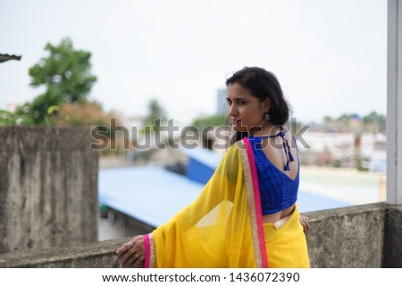 Young and beautiful Indian Bengali brunette woman in Indian traditional dress yellow sari and blue blouse is standing thoughtfully leaning on rooftop wall under blue sky with clouds. Indian lifestyle  #1436072390