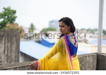 Young and beautiful Indian Bengali brunette woman in Indian traditional dress yellow sari and blue blouse is standing thoughtfully leaning on rooftop wall under blue sky with clouds. Indian lifestyle  #1436072393