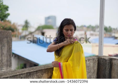 Young and beautiful Indian Bengali brunette woman in Indian traditional dress yellow sari and blue blouse is standing thoughtfully leaning on rooftop wall under blue sky with clouds. Indian lifestyle  #1436072396