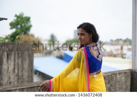 Young and beautiful Indian Bengali brunette woman in Indian traditional dress yellow sari and blue blouse is standing thoughtfully leaning on rooftop wall under blue sky with clouds. Indian lifestyle  #1436072408