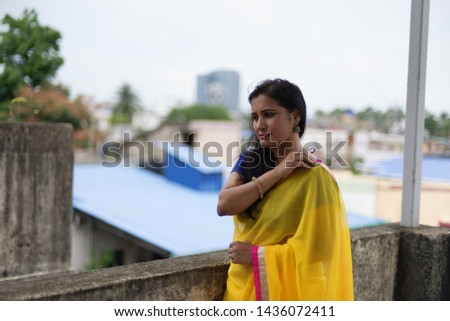 Young and beautiful Indian Bengali brunette woman in Indian traditional dress yellow sari and blue blouse is standing thoughtfully leaning on rooftop wall under blue sky with clouds. Indian lifestyle  #1436072411