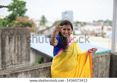 Young and beautiful Indian Bengali brunette woman in Indian traditional dress yellow sari and blue blouse is smiling while leaning on rooftop wall under blue sky with clouds. Indian lifestyle  #1436073413