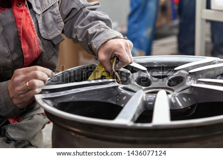 Master body repair man is working on preparing the surface of the aluminum wheel of the car for subsequent painting in the workshop, cleaning and leveling the disk with the help of abrasive material Royalty-Free Stock Photo #1436077124