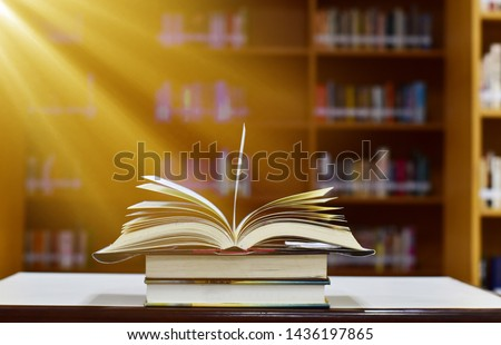 The beam shines down to the open magic book on wood table and blurred bookshelf in the library, education background. #1436197865