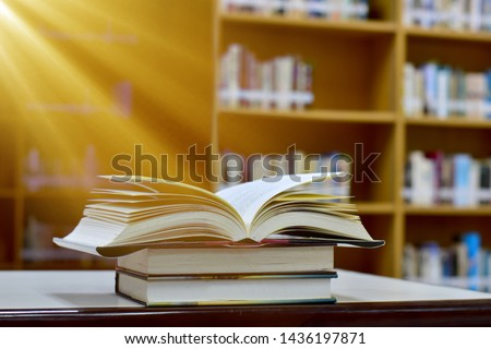 The beam shines down to the open magic book on wood table and blurred bookshelf in the library, education background. #1436197871