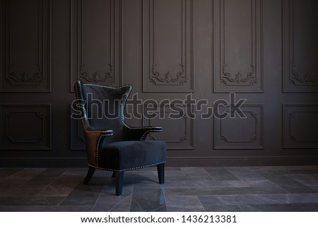 Stylish black chair against a dark gray wall. Stylish chair on wall background, copy space, fashionable interior Royalty-Free Stock Photo #1436213381
