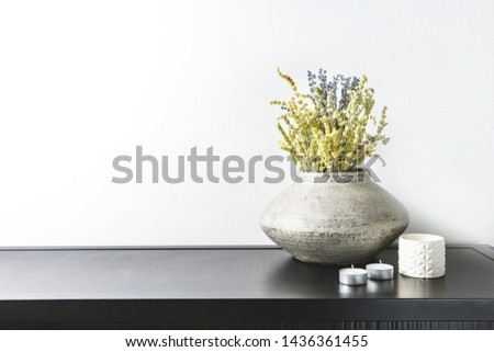 Interior design of room, mock-up, vase and lavender and lemon grass herbs bouquet, candles, white books on black table and white wall. Minimalism style.