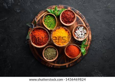 Colorful herbs and spices for cooking. Indian spices. On a black stone background. Top view. #1436469824