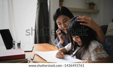 Family concept. Mom is working and taking care of her daughter too. #1436493761