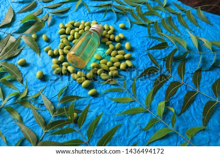 Medicinal neem leaves with essential oil over blue background #1436494172