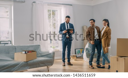 Professional Real Estate Agent Shows Bright New Apartment to a Young Couple. Successful Young Couple Ready to Become Homeowners. Spacious Bright Home with Big Windows. Royalty-Free Stock Photo #1436511659