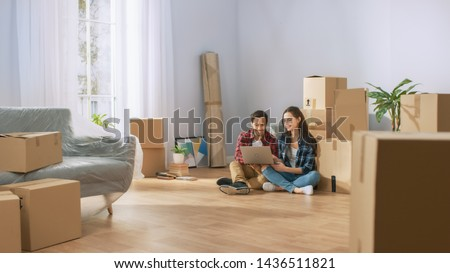 Happy Young Couple Sitting on the Floor of the Newly Rented / Purchased Apartment Use Laptop Computer. Unpacked Cardboard Boxes and Covered Furniture in the Modern Bright Sweet Home. Royalty-Free Stock Photo #1436511821