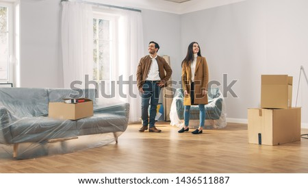 Happy and Excited Young Couple Look Around In Wonder at their Newly Purchased / Rented Apartment. Beautiful People Poses Happily. Big Bright Modern Home with Cardboard Boxes Ready to Unpack. Royalty-Free Stock Photo #1436511887