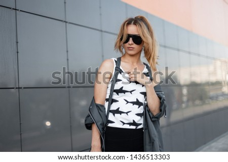 Stylish pretty young red-haired hipster woman in trendy sunglasses in trendy clothes poses in a city near a modern building. Beautiful girl on a walk on a summer day. Street fashion. #1436513303