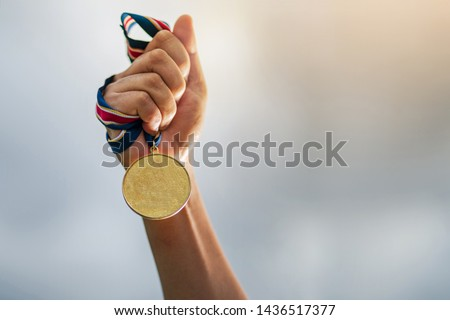 Hand holding gold medal on sky background, The winner and successful concept #1436517377