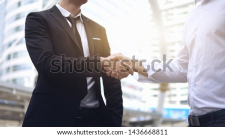Two businessmen shaking hands, outdoors #1436668811