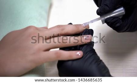 Manicure designer applying nail base before nail polish, beauty salon procedure #1436685635
